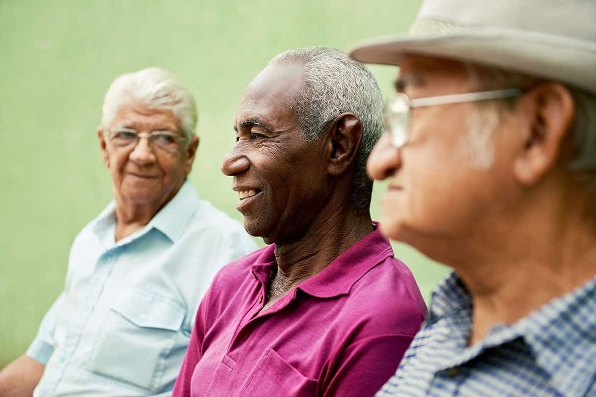 18064667 - retired elderly people and free time, group of happy senior african american and caucasian male friends talking and sitting on bench in park